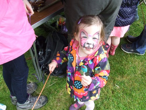 All the fun of the festival. Funny feline face on young fan of the festival.